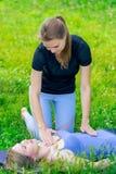 ένας πεπειραμένος εκπαιδευτής ελέγχει τα woman's αναπνέοντας κατά τη διάρκεια μιας κατηγορίας γιόγκας στοκ εικόνες