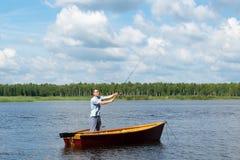 Ένα άτομο από μια βάρκα στον ποταμό αλιεύει για την περιστροφή, υπαίθριες δραστηριότητες στοκ εικόνα