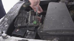 Ένα άτομο εγκαθιστά μια μπαταρία αυτοκινήτων και σφίγγει το τερματικό, χειμώνας, χιόνι, απαλλαγή μπαταριών, κινηματογράφηση σε πρ φιλμ μικρού μήκους