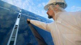 Ένα άτομο καθαρίζει τα ηλιακά πλαίσια σε μια στέγη, κλείνει επάνω απόθεμα βίντεο