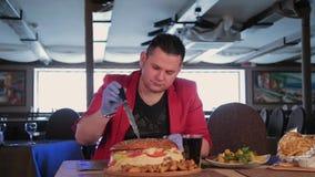 Ένα άτομο κόβει τεράστιο burger με ένα μαχαίρι απόθεμα βίντεο