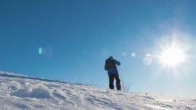 Ένα άτομο με τα ραβδιά σακιδίων πλάτης και οδοιπορίας ενάντια στο σκηνικό των χειμερινών βουνών, όμορφο ηλιοβασίλεμα, χιόνι στους απόθεμα βίντεο
