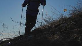 Ένα άτομο με τα ραβδιά σακιδίων πλάτης και οδοιπορίας ενάντια στο σκηνικό των χειμερινών βουνών, όμορφο ηλιοβασίλεμα, χιόνι στους φιλμ μικρού μήκους