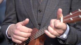 Ένα άτομο σε ένα κοστούμι που παίζει το ukulele απόθεμα βίντεο