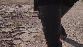 Ένα άτομο στις μπότες δέρματος είναι στο ραγισμένο έδαφος έρημος κλείστε επάνω απόθεμα βίντεο