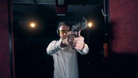 Ένα άτομο χρησιμοποιεί ένα πυροβόλο όπλο για να στοχεύσει σε μια σειρά πυροβολισμού, κλείνει επάνω απόθεμα βίντεο