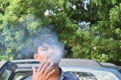 Ένα άτομο που καπνίζει με μια τοποθέτηση στοκ εικόνες