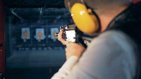 Ένα άτομο που στοχεύει έναν στόχο με ένα τουφέκι σε μια σειρά πυροβολισμού, πίσω άποψη φιλμ μικρού μήκους