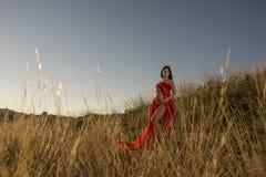 Ένα έγκυο νέο κόκκινο ντυμένο κορίτσι που στέκεται υπαίθριο στη χλόη στοκ φωτογραφία με δικαίωμα ελεύθερης χρήσης