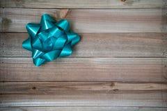 Ένα ενιαίο τόξο συσκευασίας δώρων κιρκιριών μπλε σε ένα καφετί ξύλινο υπόβαθρο Χρήσιμος για τις έννοιες γιορτών γενεθλίων ή Χριστ στοκ εικόνα με δικαίωμα ελεύθερης χρήσης