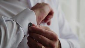 Ένα επιτυχές άτομο στερεώνει τις συνδέσεις μανσετών στο πουκάμισό του, κινηματογράφηση σε πρώτο πλάνο απόθεμα βίντεο