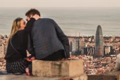 Ένα ζεύγος φιλά μπροστά από τις απόψεις της Βαρκελώνης, Ισπανία Είναι χρόνος ηλιοβασιλέματος στοκ εικόνα