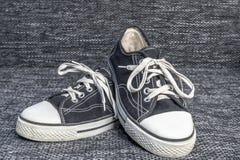 Ένα ζευγάρι των παλαιών πάνινων παπουτσιών σε ένα υπόβαθρο καμβά στοκ εικόνες με δικαίωμα ελεύθερης χρήσης
