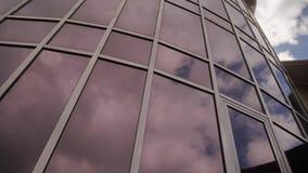 Ένα θαυμάσιο κτήριο φιαγμένο από γυαλί με τις αντανακλάσεις του ουρανού και των σύννεφων σε το απόθεμα βίντεο