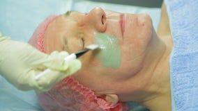 Ένα θηλυκό cosmetologist στα γάντια εφαρμόζει μια θεραπευτική μάσκα αργίλου σε ένα πρόσωπο ατόμων s με μια βούρτσα φιλμ μικρού μήκους