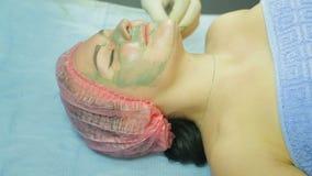 Ένα θηλυκό cosmetologist στα γάντια εφαρμόζει μια μάσκα επεξεργασίας σε ένα πρόσωπο ατόμων s με μια βούρτσα φιλμ μικρού μήκους