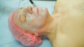 Ένα θηλυκό cosmetologist που φορά τα γάντια εφαρμόζει μια μάσκα φυκιών σε ένα πρόσωπο ατόμων s με μια βούρτσα Πλάγια όψη φιλμ μικρού μήκους