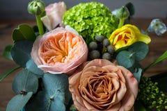 Ένα καλάθι των όμορφων λουλουδιών σε ένα ξύλινο υπόβαθρο στοκ εικόνα