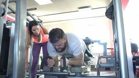 Ένα καυκάσιο άτομο με μια γενειάδα συμμετέχει στη γυμναστική με έναν μεμονωμένο εκπαιδευτή σε έναν γυμναζόμενο μυών ποδιών, κάμψη απόθεμα βίντεο