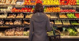Ένα κινούμενο πλαίσιο μιας νέας γυναίκας brunette που στέκεται μπροστά από μια σειρά των προϊόντων σε ένα μανάβικο φιλμ μικρού μήκους