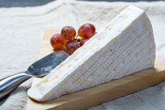 Ένα κομμάτι του γαλλικού μαλακού τυριού Brie με την άσπρη φόρμα και την ισχυρή μυρωδιά, που εξυπηρετείται με τα φρέσκα σταφύλια στοκ εικόνα