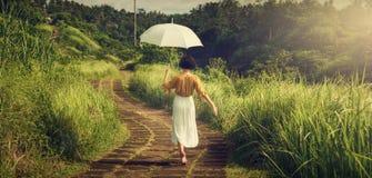 Ένα κορίτσι σε ένα άσπρο φόρεμα στην πορεία του κοριτσιού καλλιτεχνών με μια ομπρέλα Ταξίδι του Μπαλί tropics Περίπατος κορυφογρα στοκ εικόνα