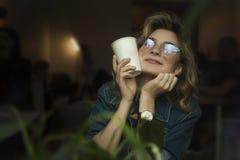 Ένα κορίτσι σε έναν καφέ με ένα lap-top εργάζεται σε μια άνετη θέση με ένα φλιτζάνι του καφέ, παίρνει την ευχαρίστηση Η έννοια στοκ εικόνες με δικαίωμα ελεύθερης χρήσης