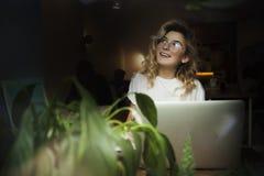 Ένα κορίτσι σε έναν καφέ με ένα lap-top εργάζεται σε μια άνετη θέση με ένα φλιτζάνι του καφέ, παίρνει την ευχαρίστηση Η έννοια στοκ εικόνες