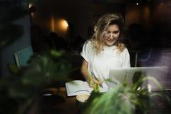 Ένα κορίτσι σε έναν καφέ με ένα lap-top εργάζεται σε μια άνετη θέση με ένα φλιτζάνι του καφέ, παίρνει την ευχαρίστηση Η έννοια στοκ εικόνα με δικαίωμα ελεύθερης χρήσης