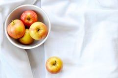 Ένα κύπελλο των οργανικών μήλων, αριστερά του κέντρου, σε ένα άσπρο υπόβαθρο στοκ φωτογραφία με δικαίωμα ελεύθερης χρήσης