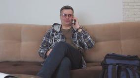 Ένα μέσης ηλικίας άτομο κάθεται σε έναν καναπέ σε ένα δωμάτιο ξενοδοχείου και μιλά στο τηλέφωνο, δίπλα σε τον είναι ένα μπλε σακί απόθεμα βίντεο