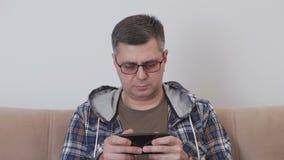 Ένα μέσο ηλικίας άτομο στα γυαλιά χρησιμοποιεί κινητό Διαδίκτυο σε ένα smartphone καθμένος σε έναν καναπέ σε ένα δωμάτιο απόθεμα βίντεο