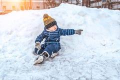 Ένα μικρό αγόρι 3-5 χρονών, το χειμώνα έξω snowdrift και ένα χιόνι, που στηρίζονται σε ένα Σαββατοκύριακο, που κάθεται σε ένα μπλ στοκ εικόνες