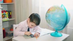 Ένα μικρό παιδί υπολογίζει εκ νέου την αποταμίευσή του σε έναν υπολογιστή απόθεμα βίντεο