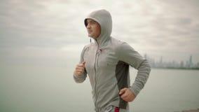 Ένα νέο αθλητικό άτομο που τρέχει στα πλαίσια της πόλης και της λίμνης, σε αργή κίνηση απόθεμα βίντεο