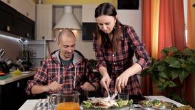 Ένα νέο ζεύγος μαγείρεψε το γεύμα, σαλάτες, λαχανικά, ένα νέο κορίτσι έκοψε ένα τηγανισμένο κοτόπουλο απόθεμα βίντεο