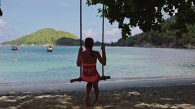 Ένα νέο κορίτσι σε ένα κοστούμι λουσίματος, που ταλαντεύεται σε μια σπιτική ταλάντευση σχοινιών, σε μια αμμώδη παραλία στην μπλε  απόθεμα βίντεο