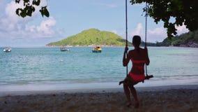 Ένα νέο κορίτσι σε ένα κοστούμι λουσίματος, που ταλαντεύεται σε μια σπιτική ταλάντευση σχοινιών, σε μια αμμώδη παραλία στην μπλε  φιλμ μικρού μήκους