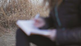 Ένα νέο κορίτσι σε μια σκοτεινή συνεδρίαση σακακιών από τον ποταμό σε ένα απόγευμα άνοιξη παίρνει τις σημειώσεις με μια μάνδρα σε απόθεμα βίντεο
