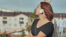 Ένα νέο κορίτσι στα άσπρα ακουστικά με την ευχαρίστηση ακούει τη μουσική σε ένα θερμό θερινό βράδυ φιλμ μικρού μήκους