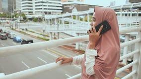 Ένα νέο μουσουλμανικό κορίτσι σε ένα ρόδινο hijab σχηματίζει έναν αριθμό και μιλά στο τηλέφωνο πέρα από την οδική κυκλοφορία στο  απόθεμα βίντεο