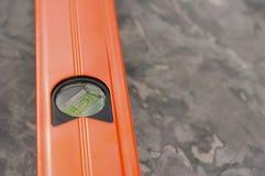 Ένα νέο πορτοκαλί επίπεδο οικοδόμησης αργιλίου στοκ φωτογραφίες