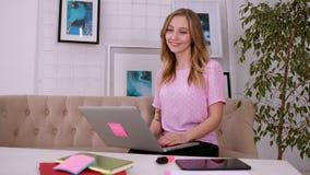 Ένα όμορφο ελκυστικό κορίτσι με τα ξανθά μαλλιά της ευρωπαϊκής εμφάνισης σε μια ρόδινη μπλούζα εξετάζει τη κάμερα και εργάζεται σ φιλμ μικρού μήκους