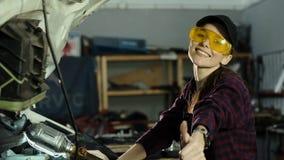 Ένα όμορφο κορίτσι brunette, ένας μηχανικός συντήρησης αυτοκινήτων, που φορά μια ΚΑΠ και ένα πουκάμισο καρό, επισκευάζει τη μηχαν απόθεμα βίντεο