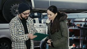 Ένα όμορφο κορίτσι brunette, ένας πελάτης ενός κέντρου υπηρεσιών αυτοκινήτων, παίρνει ένα αυτοκίνητο από μια επισκευή και υπογράφ απόθεμα βίντεο