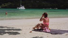 Ένα όμορφο νέο κορίτσι κάθεται στην παραλία και λερώνει το σώμα της με sunscreen απόθεμα βίντεο