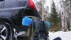 Ένα σακίδιο πλάτης ταξιδιού με ένα χαλί στέκεται δίπλα στο αυτοκίνητο διασταυρώσεων φιλμ μικρού μήκους