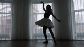 Ένα στούντιο στο λυκόφως Μια σκιαγραφία του νέου ballerina γυναικών που εκπαιδεύει την που περιστρέφει απόθεμα βίντεο