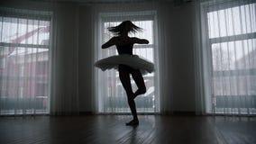 Ένα στούντιο στο λυκόφως Μια σκιαγραφία του νέου ballerina γυναικών που εκτελεί μια χαριτωμένη περιστροφή φιλμ μικρού μήκους