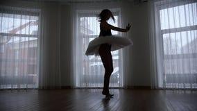 Ένα στούντιο στο λυκόφως Μια σκιαγραφία του νέου ballerina γυναικών που εκτελεί μια περιστροφή μπροστά από το παράθυρο απόθεμα βίντεο
